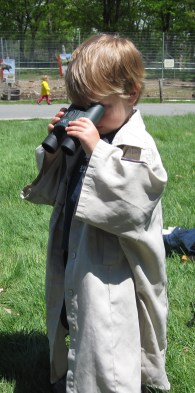A little boy tries on the biologist shirt and binoculars at the Endangered Species Day event booth. Credit: USFWS