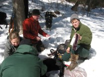 These biologists are working on the mother bear's radio collar. She's been safely sedated for the brief study. Credit: USFWS