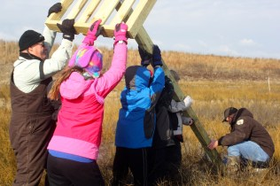 Biologists and volunteers raise an osprey nest platform at Poplar Island