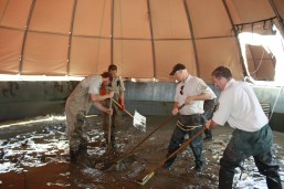Staff working to clean sediment that infiltrated fish ponds.