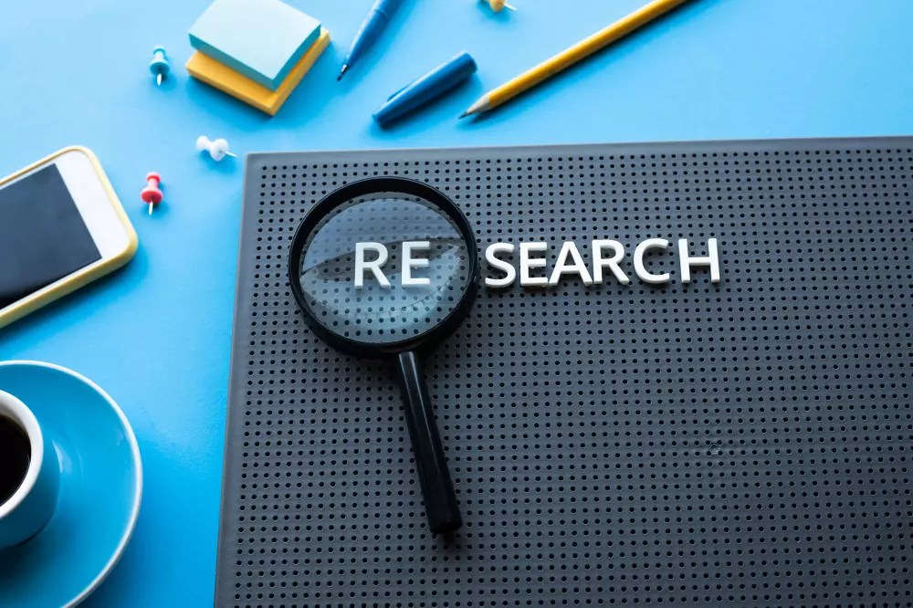 Pinboard with the word 'research' and a loupe.