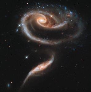 Kahden galaksin muodostama 'ruusu' Arp 273. Pienemmän arvellaan kulkeneen isomman galaksin läpi ja aiheuttaneen sen muotoon vääristymiä. Kuva: ESA Hubble