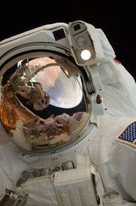 Hubblen huoltotyö käynnissä 2009, kuvassa astronautti John Grunsfeld ja hänen visiiristään heijastuu työpari Andrew Feustel. Kuva: ESA Hubble.
