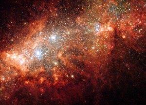 Läheisessä kääpiögalaksissa NGC 1569 tapahtuu tähtien syntymistä ja supernova-räjähdyksiä, jotka saavat vetykaasun hehkumaan. Uudet tähdet puhaltavat ikäänkuin kuplia kaasupilveen. Kuva: ESA Hubble.