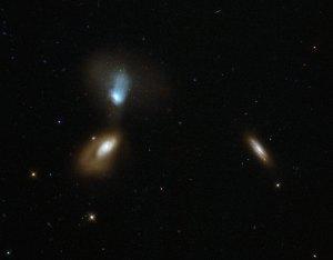 Tässä on menossa kahden galaksin kohtaaminen, jonka aikana gravitaatiovoimat vääristävät kummankin galaksin muotoa. Kolmas galaksi oikeassa reunassa ei kuulu samaan soppaan ja on muodoltaan säännöllinen. Kuva: ESA Hubble.