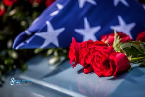 flag on casket at graveside with flroal spray Ryan hender photography