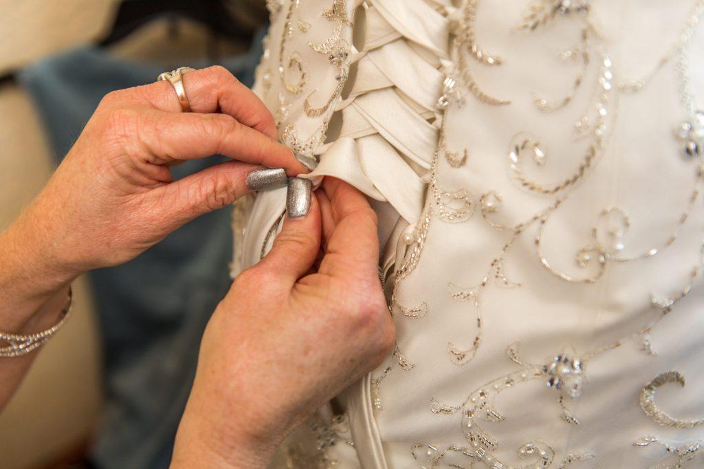 Mother of bride tying up back of Bride's dress