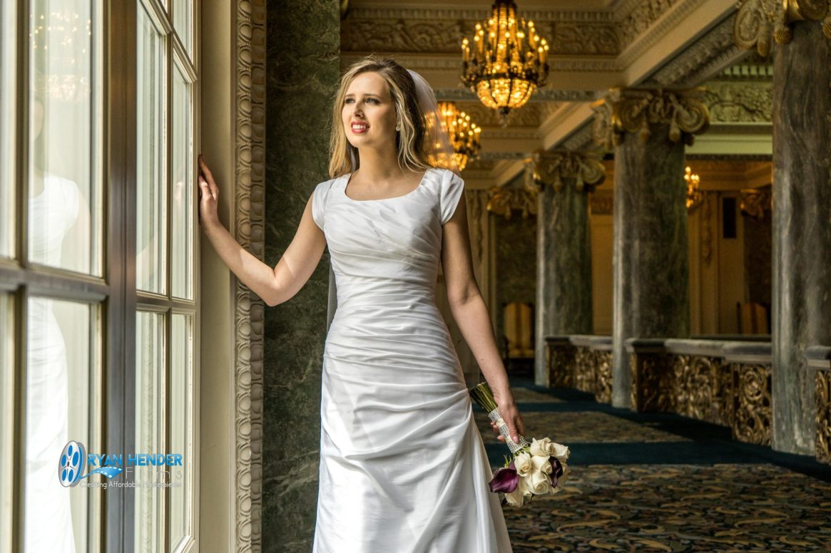 bride standing at window wedding photography