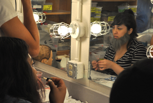 Art & Art History senior Priscilla Ruiz, right, examines her beard in the mirror during a Theatrical makeup class this summer. Ruiz and 17 other UT Arlington students learned how to manipulate hair and makeup for stage and film actors. (Photo by James Dunning)