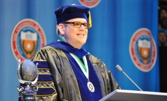 Assistant Dean Les Riding-In speaks Friday, May 15, during the College of Liberal Arts' Spring 2015 Commencement at College Park Center. (Photo by James Dunning/COLA Communications)