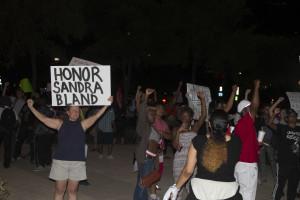 Protestors stand outside the Omni Hotel in downtown Dallas.