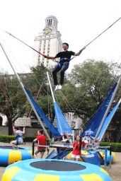 A participant bungee jumps in front of the Tower.