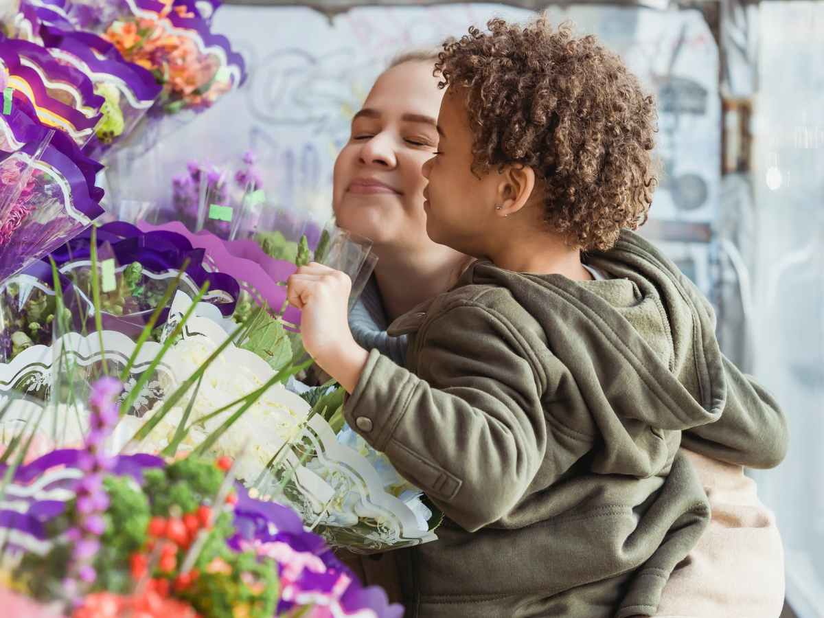 positive mother and black son enjoying smell of fresh flowers
