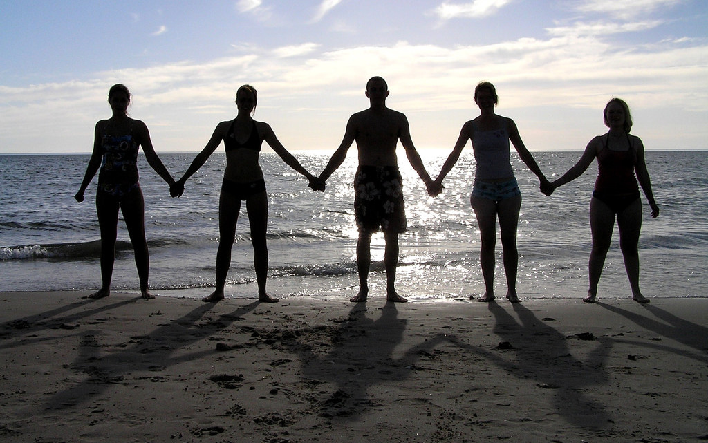 Silhouette of people holding hands on the beach