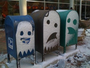 Snow faces on three mailboxes