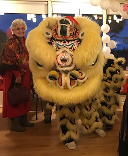 Woman standing beside a lion dancer with the head in the foreground