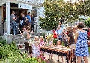 Picture of children and adults gathering outside the fellowship with flowers