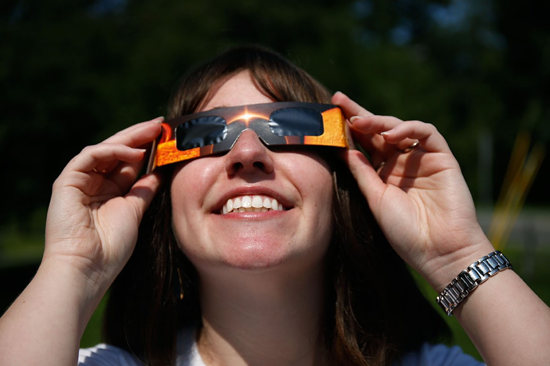 Valley News night editor Amanda Newman takes a peek at the solar eclipse on Monday, August 21, 2017, at the Valley News office in West Lebanon, N.H.