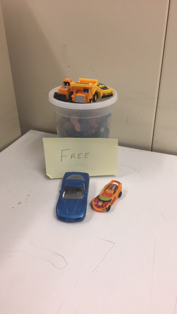 A collection of small toys, including some brightly colored cars, being offered up to 'Valley News' staffers.
