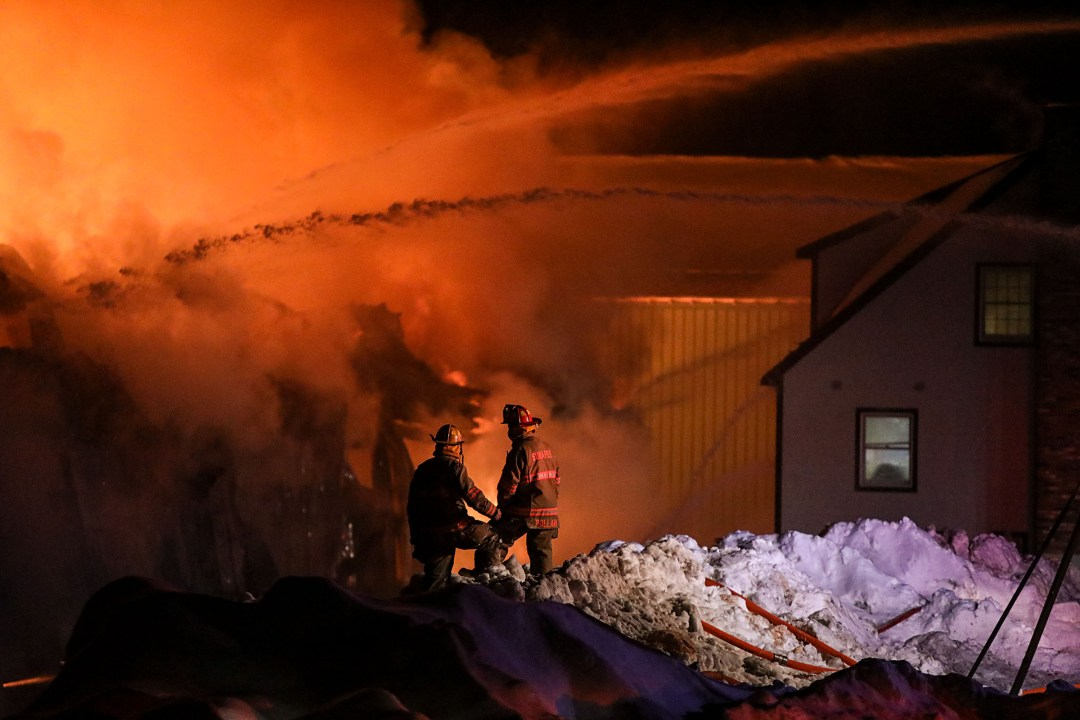 Two members of the Sunapee Fire Department watch as a fully involved lumberyard fire burns on Wednesday, Jan. 3, 2018, at Durgin and Crowell Lumber Co. in Springfield, N.H. (Valley News - Charles Hatcher) Copyright Valley News. May not be reprinted or used online without permission. Send requests to permission@vnews.com.