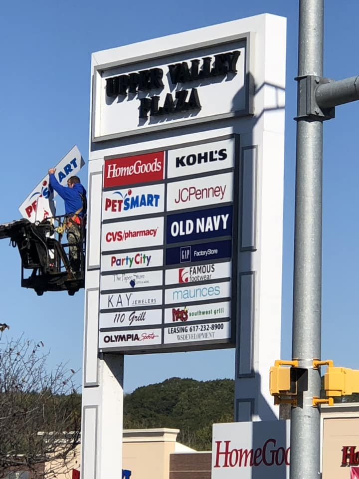 Workers change out the stores listed on a sign outside of the Upper Valley Plaza on Friday. Old Navy and 110 Grill will be opening locations in the Route 12A shopping center.  (Photograph courtesy Tina Hebb)