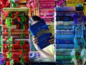 Picture of Cait aka Paperfury behind a book stack