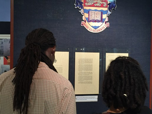 Visitors read the UWI Honorary Degree citation to Emperor Haile Selassie during a commemorative exhibition at the UWI Museum