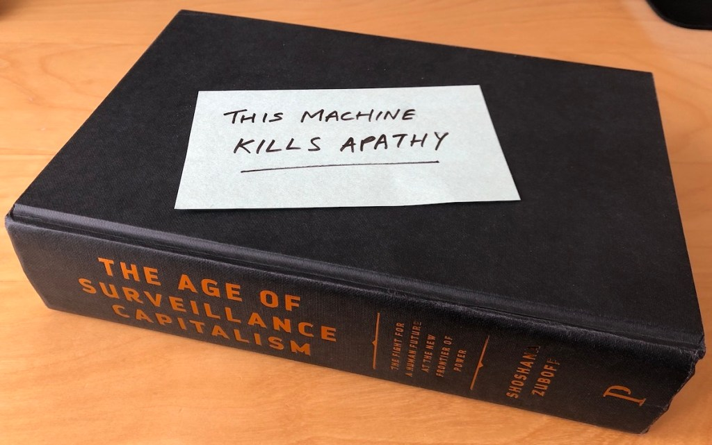 'The age of surveillance capitalism' book, with post-it note on top saying 'this machine kills apathy'