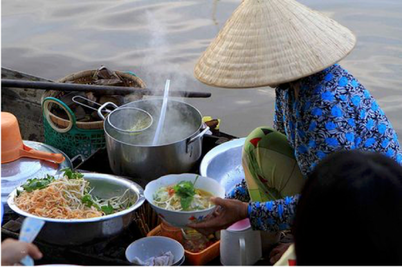 A Vietnamese lady making noodles on a boat