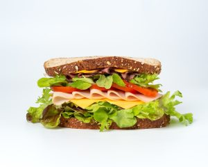 a sandwich with cold meat, cheese, tomato and lettuce