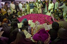 Mourners at the grave of Benazir Bhutto in the week following her death. She is buried beside her father in the family mausoleum near Naudero in the interior of the Sindh province.