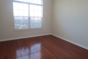 Front bedroom with large window and hardwood floor