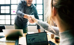 man and woman shaking hands in office - Increased Productivity and Reduced Costs: 2 Key Benefits of an IT Managed Service Provider