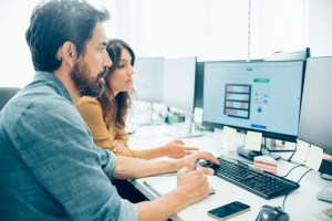 man and woman working infront of computer - 14 Ways IT Security Consultants Can Help Your Business