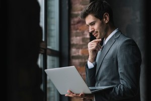 business man smiling with laptop on hand - How to Make a Smooth Transition to Office 365