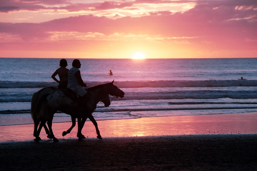 Horseback riding at sunset on the beach in Costa Rica by Vacancy Rewardsa