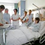 kórházban a beteg ágya körül orvos és nővérek