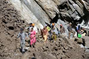 Stranded Hindu pilgrims and villagers make their way across a landslide as they make their way down the mountain in Govindghat following flash floods in northern Uttarakhand