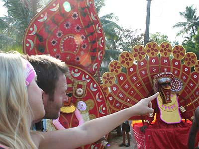 Foreign tourists watching the actions of a `Theyyyam' during the Cochin Carnival