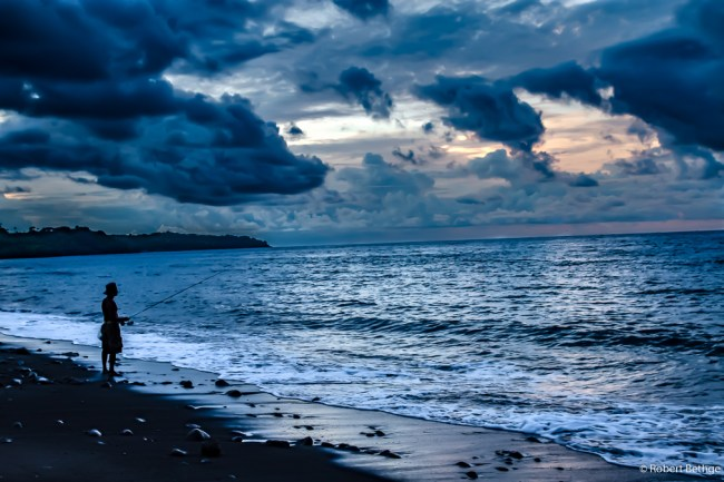 fisher on deserted beach on Bali at black sand beaches