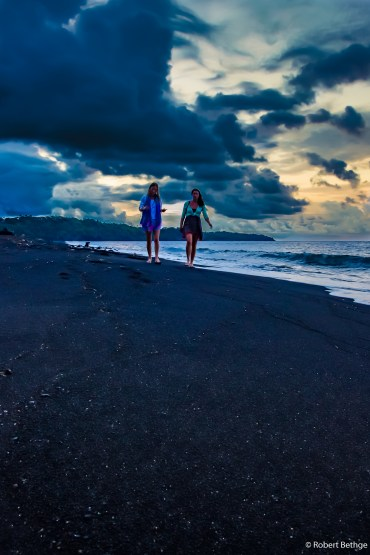 two beautiful girls walking along a black sand beach in the sunset
