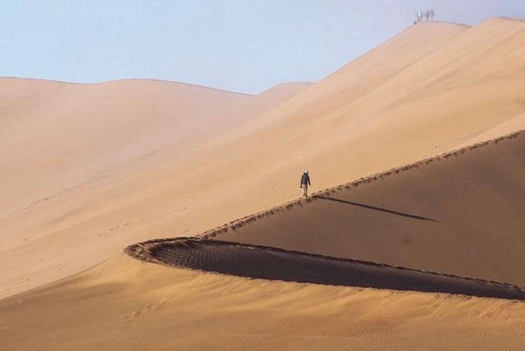 Primeros turistas ascendiendo dunas en Sossusvlei, a primera hora de la mañana aún con niebla. Desierto de Namibia