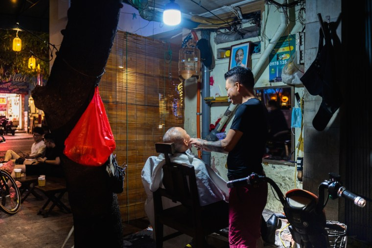 Peluquería improvisada en la calle en Hanoi