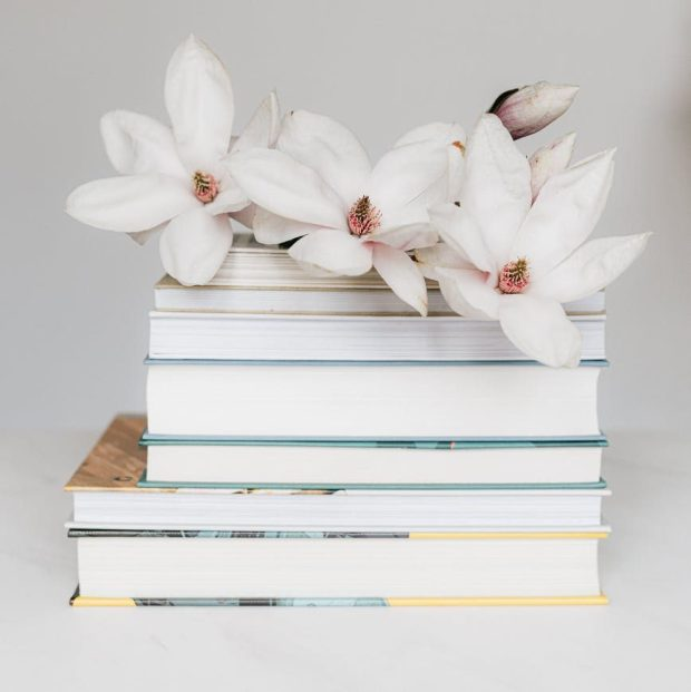stack of books with magnolia flower on white table