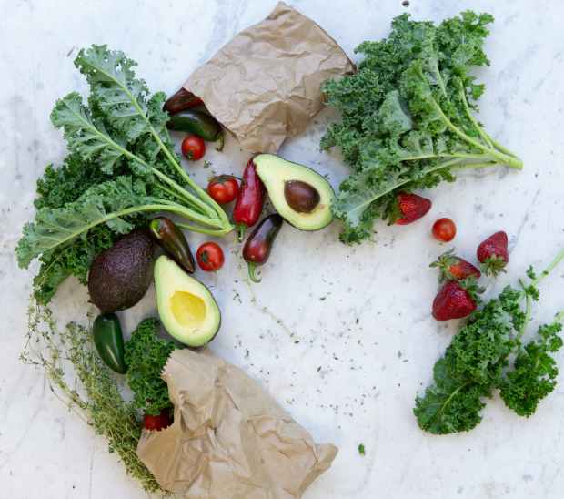 flat lay photo of fruits and vegetables with brown paper bags contrasted against a beautiful marble surface