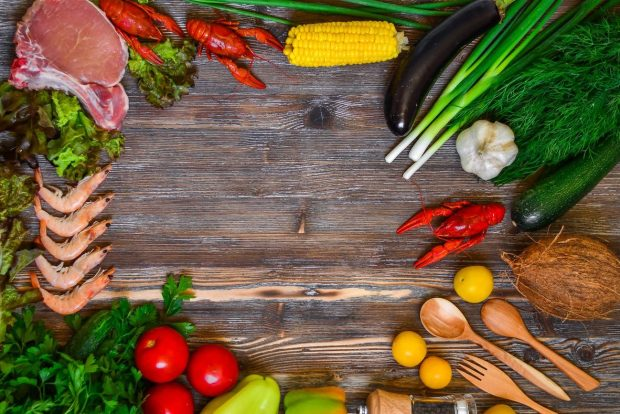 vegetables, fruit, meat and fish on cutting board