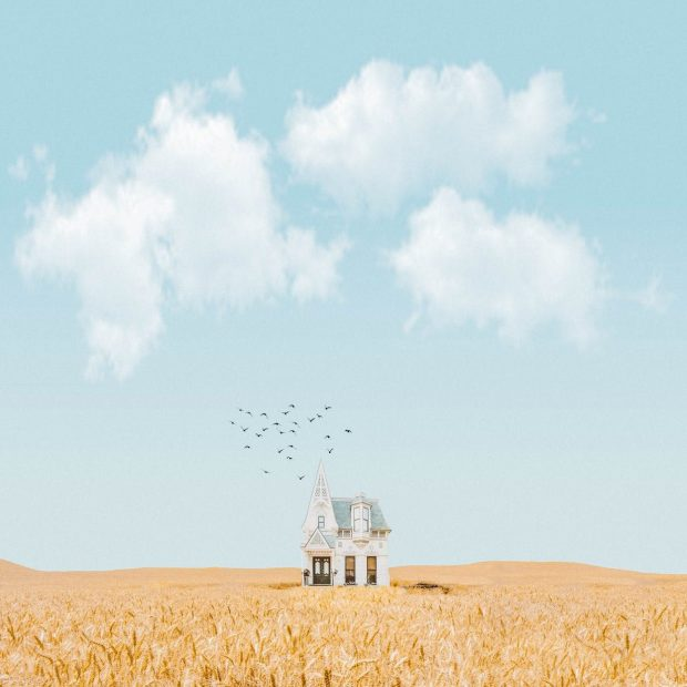 house in the middle of crop field with a blue sky and white clouds, a peaceful image much like the mind when practicing gratitude