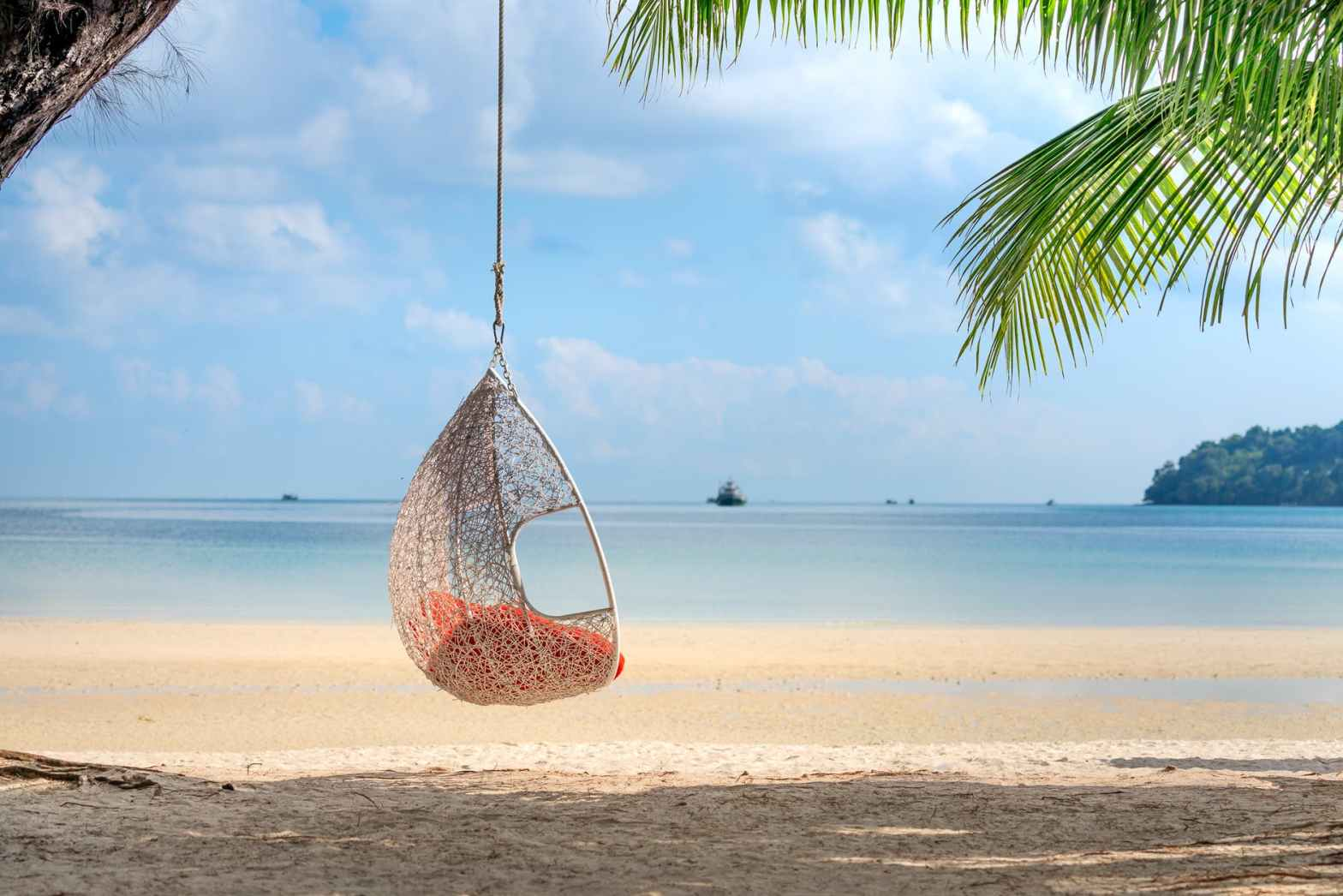 wicker hanging egg chair on picturesque seaside
