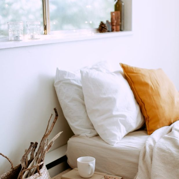 cosy bedroom interior with natural lighting, plush pillows, neutral colours, firewood and a tea cup
