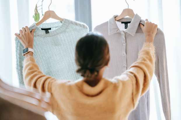 woman choosing between clothes in store, take your time for sustainable shopping - ask yourself if you need it